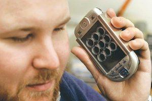 A képen a MOST szoftvert futtató braille maszkkal ellátott PDA látható kézben tartva.